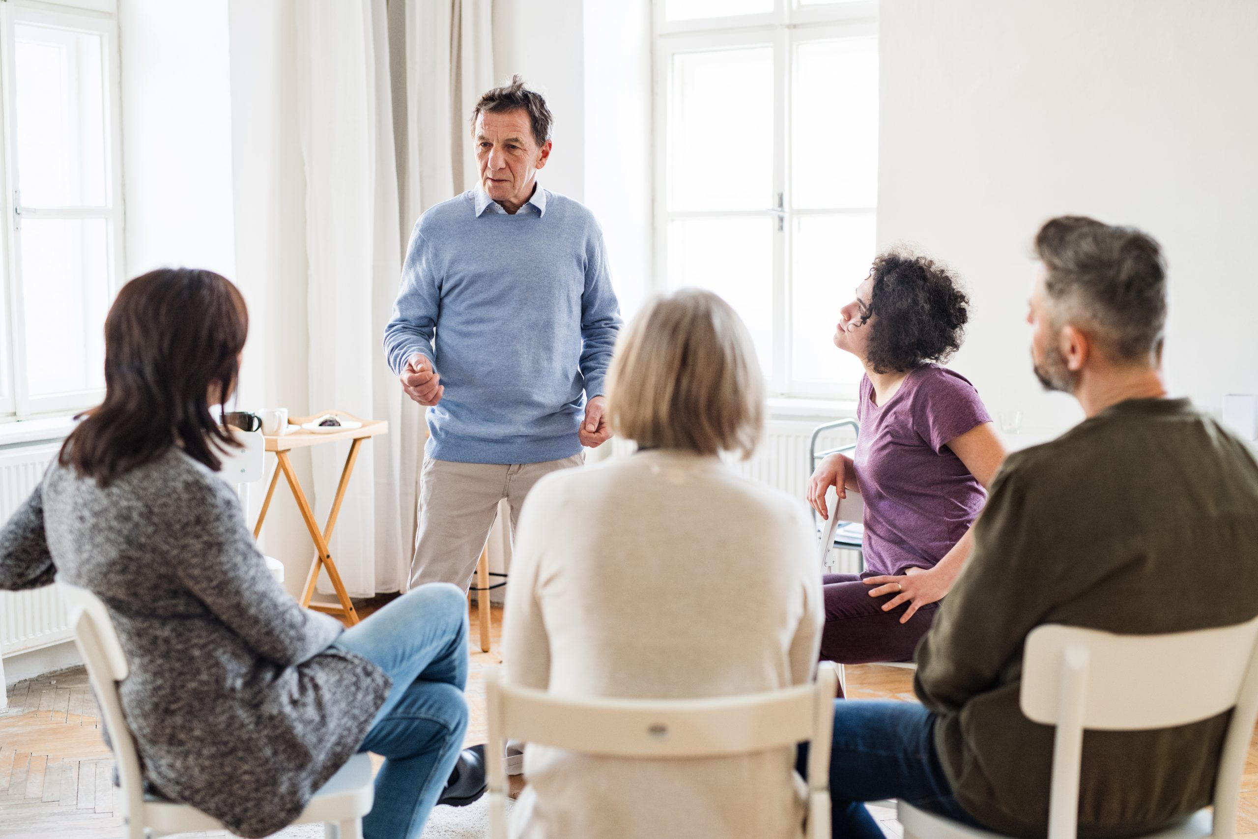 A mature man standing and talking to other people during group therapy.